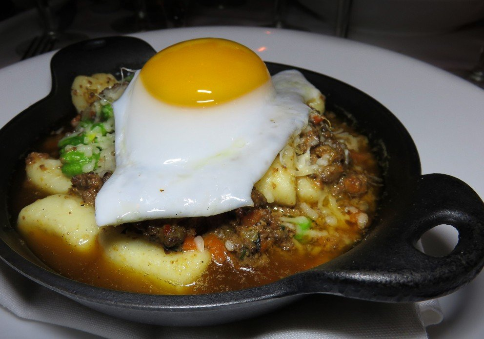 Duck Bolognese over gnocchi with favas and a cute duck egg